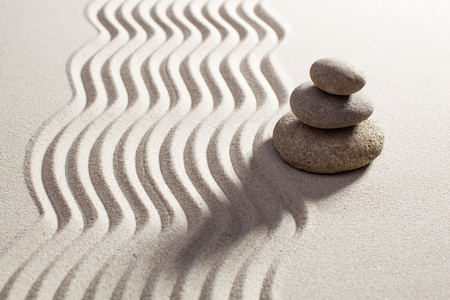 pebbles in balance set next to waves in sand for progression or spirituality concept Reklamní fotografie