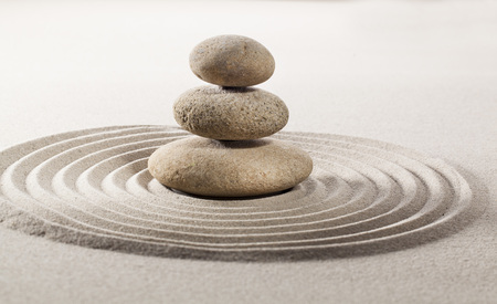 three stones or pebbles in balance in the middle of pure waves in sand for concept of concentration or wellbeing Reklamní fotografie