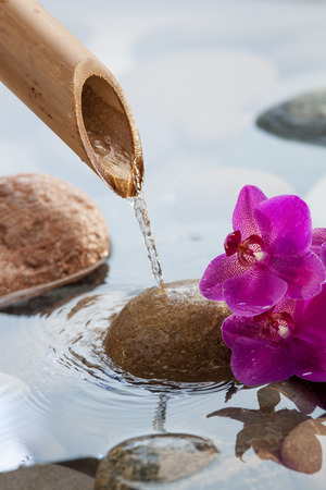 peace pipe: hydrating peaceful water for relaxation with beautiful pebbles, pink orchids and bamboo pipe for source of peace and beauty Stock Photo