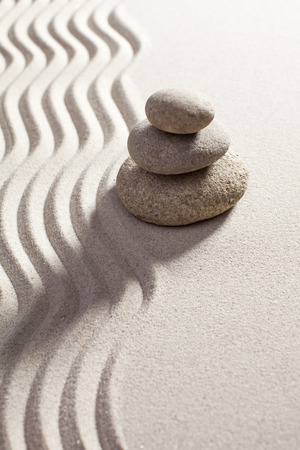 progression: stones in balance next to waves in sand for progression or spirituality concept Stock Photo