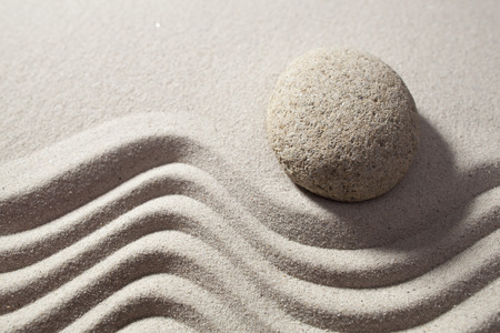 sinuous: top view of round stone before sinuous path in zen sand for philosophy of life set on the border waves