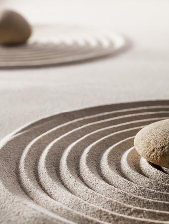 piedras zen: piedras o guijarros en el medio de las ondas puras en la arena para el concepto de tranquilidad o bienestar
