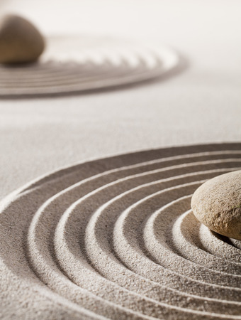 zen rocks: stones or pebbles in the middle of pure waves in sand for concept of tranquillity or wellness Stock Photo