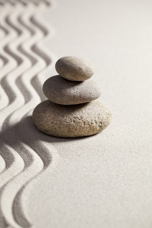pebbles in balance set next to waves in sand for contemplation or spirituality concept