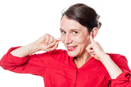 embarassment: noise and hearing concept - cheeky young woman smiling in plugging her fingers in ears to ignore problems, white background