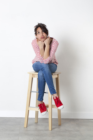 puffed cheeks: imagination concept - pouting 20s multi-ethnic woman with cheeks puffed out looking bored, sitting on a stool,looking up to escape