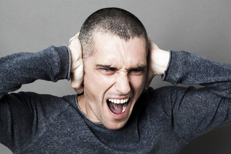 noise and hearing concept - enraged young man screaming, plugging his ears to refuse listening to problems or stress, contrast effects