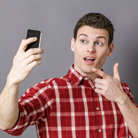 taking photo: male selfie - relaxed young sportsman taking selfie for seduction over gray background studio