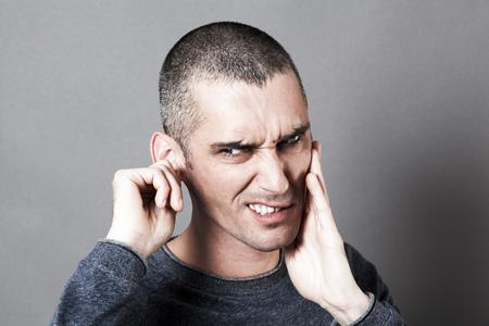 dolor de oido: el ruido y el concepto de audiencia - nervioso joven que sufre de dolor de muelas o dolor de oído, tocando su cara de dolor, efectos de contraste Foto de archivo