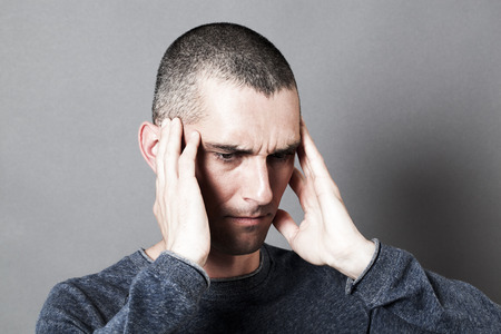 noise and hearing concept - upset young man suffering from painful earache or headache, covering his temples for pain, contrast effects