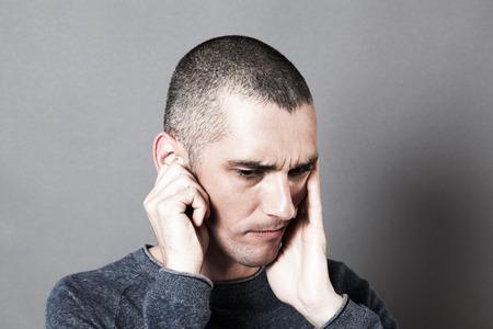 dolor de oido: el ruido y el concepto de audiencia - el pensamiento del hombre joven que sufre de dolor de oído que cubren las orejas y la cara, contrastar los efectos Foto de archivo
