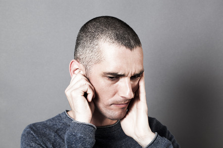 deafening: noise and hearing concept - thinking young man suffering from earache covering his ears and face, contrast effects