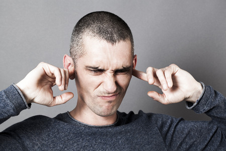 plugging: noise and hearing concept - disgusted young man plugging his ears to refuse listening to problems or noise, contrast effects