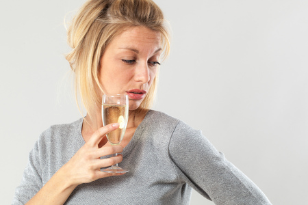 tipsy: female drinker - disgusted young blond woman drinking a wine glass suffering from booze nausea and headache, gray background
