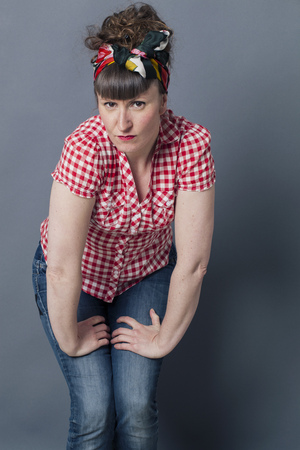 leaning forward: seduction concept - portrait of a frowning young woman with retro hairstyle and fashion leaning forward to camera, gray background studio