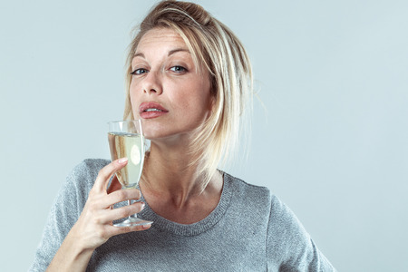 tipsy: female drinker - tipsy depressed young blond woman drinking a wine glass suffering from booze addiction, contrast effects
