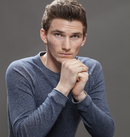 stubborn: shyness concept - portrait of a reserved young man acting stubborn with face leaning on his hands, gray background studio Stock Photo