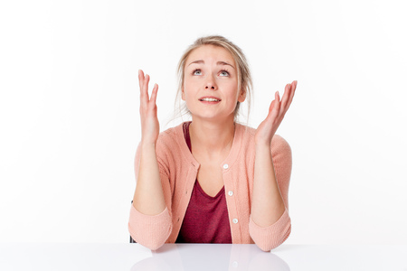 imagination concept - smiling 20s blond woman with hands up enjoying thinking about an inspiring miracle, sitting on a white desk,looking up to escape, white background