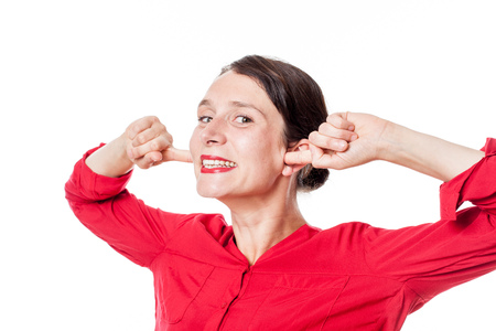 embarassment: noise and hearing concept - childish young woman smiling in plugging her fingers in ears to ignore problems, white background