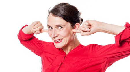 embarassment: noise and hearing concept - happy young woman smiling in plugging her fingers in ears to ignore problems, white background Stock Photo