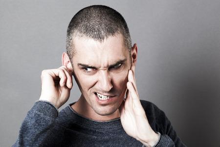 dolor de oido: el ruido y el concepto de audiencia - hombre joven extraño que sufren de dolor de oídos o tinnitus, tapándose los oídos para el dolor, efectos de contraste