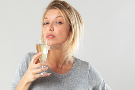 jaded: female drinker - tipsy young blond woman drinking a flute of bubbly wine suffering from booze addiction, gray background
