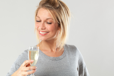 the drinker: female drinker - chic beautiful young blond woman enjoying drinking a flute of bubbly wine to celebrate her success at party, gray background Stock Photo