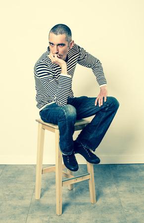 decepci�n: concepto de reflexi�n - deprimido 30s hombre sentado en un taburete que expresa la frustraci�n, el aburrimiento y la decepci�n con su lenguaje corporal, efectos verdes en estudio