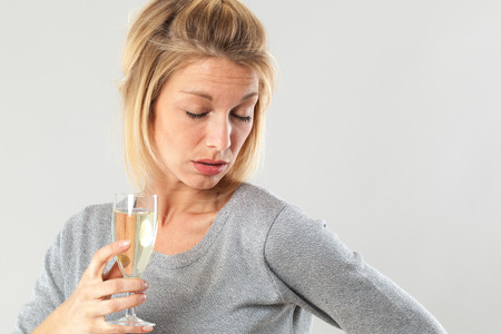 closing eyes: female alcoholism - drunk young blond woman holding a flute of bubbly wine,closing eyes, suffering from alcohol side effects, gray background