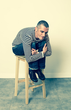 leaning forward: reflection concept - smiling 30s man sitting and leaning forward on a stool relaxing for satisfaction, green effects in studio Stock Photo