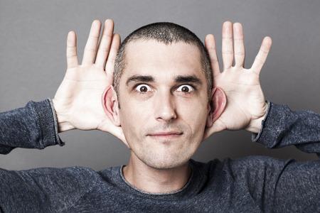 호기심과 청각 개념 - 자신의 귀 크기를 강조 장난 젊은 남자가 효과를 대비, 새로운 아이디어와 기회에 넓은 개방합니다