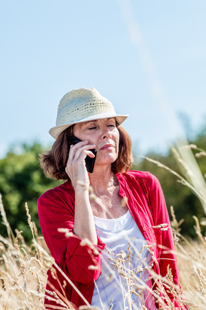 50s: outdoors communication - sad 50s woman listening conversation on mobile phone in the middle of high dry grass,summer daylight Stock Photo