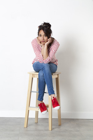 boredom concept - young multi-ethnic girl sitting on a stool, face leaning on hands to express her disappointment for the summer