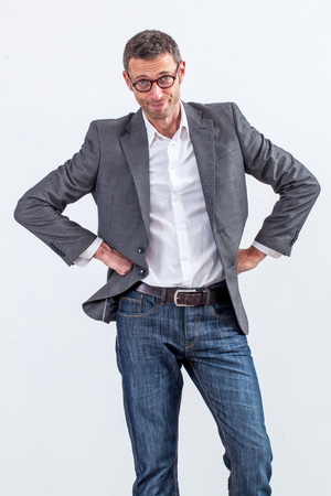 self assurance: reflection concept - smiling 40s businessman standing with hands on hips for self-assurance and entrepreneurship, white background studio Stock Photo