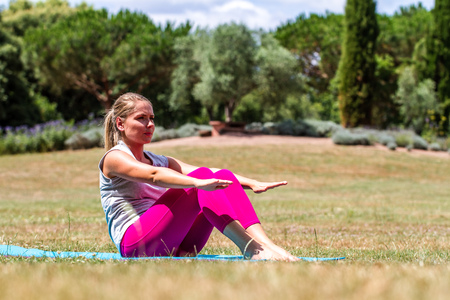 muscle toning: training outdoors - sporty young blond woman working out on her abs and muscles on an exercise mat in summer grass in park Stock Photo