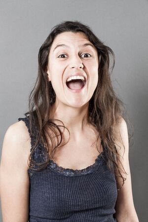laughter: female natural laughter portrait - excited young woman with natural fine hair bursting out laughing over gray background, studio shot