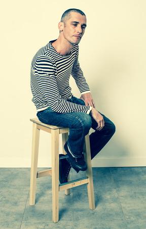 desilusion: concepto de reflexión - 30s infeliz hombre sentado en un taburete que expresa la tristeza, resignación y decepción con su lenguaje corporal, efectos verdes sombrías en estudio