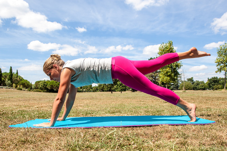 laying abs exercise: gym and fitness outside - young blond woman working out to loose weight, exercising her abs and legs on an exercise mat over sunny blue sky and dried grass