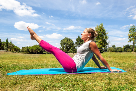 keep fit: fitness and gym outside - active young blond woman working out to keep fit, exercising her toned legs and abs on an exercise mat over sunny blue sky