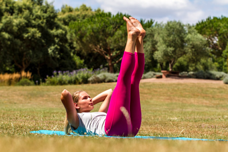 laying abs exercise: training outdoors - young blond woman exercising, toning up muscles of legs and abs on summer grass in park,  sunny daylight Stock Photo