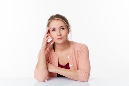 paciencia: la reflexión concepto - que se trate hermosa mujer rubia sentada en un escritorio escasa paciencia y tranquilidad, estudio de fondo blanco Foto de archivo