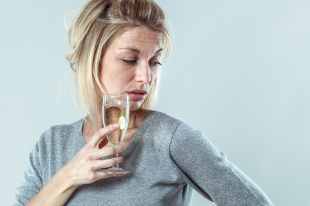 the drinker: female drinker - depressed young blond woman drinking a wine glass suffering from booze nausea and headache, contrast effects