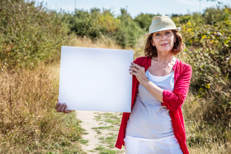 self assurance: nature teasing - beautiful 50s woman with summer hat holding a white blank panel to write message on,walking on countryside path