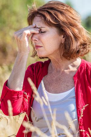 outdoors illness - beautiful mature woman having headache for rhinitis,allergies or hay fever reaction,summer daylight Stock Photo
