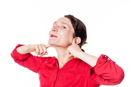 awkwardness: Noise and Hearing concept - mocking young woman smiling in plugging her fingers in ears to ignore problems, white background Stock Photo