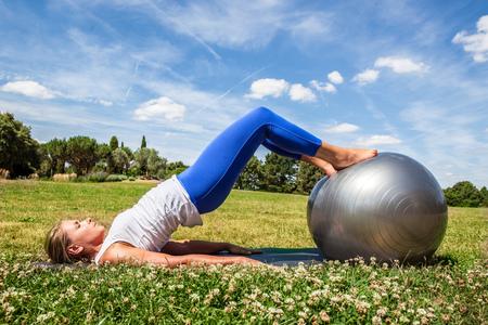 pies bonitos: al aire libre ejercicio de pilates - mujer joven rubia que hace la aptitud, tonificar el estómago con los pies en deportes de pelota en la hierba verde, luz de día de verano