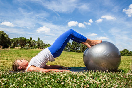 pretty feet: outdoors pilates exercise - young blond woman doing fitness, toning stomach with feet on sports ball in green grass, summer daylight