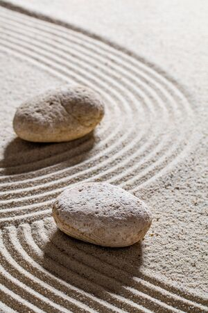 inner peace: zen sand still-life - stones set on sinuous lines for concept of change or separation with inner peace