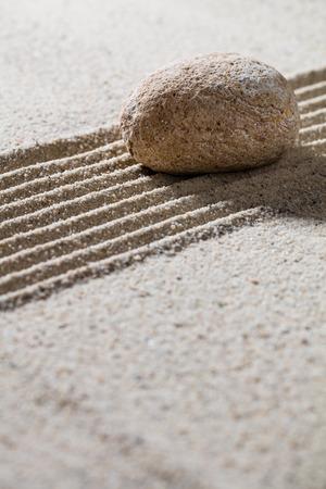 progression: zen sand still-life - textured pebble on straight lines for concept of meditation or progression, closeup Stock Photo