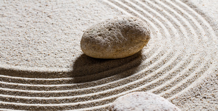 inner peace: zen sand still-life - textured stones set on sinuous waves for concept of flexibility or suppleness with inner peace